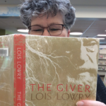 Photo of staffer Nancy holding up the book The GIver