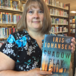Staff member Dawn holding a copy of the book Shadow Play
