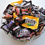 Glass bowl holding various packaged small candy.