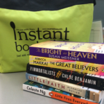 Photo of books stacked in front of green canvas bag
