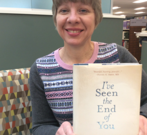 Staff person holding recommended book